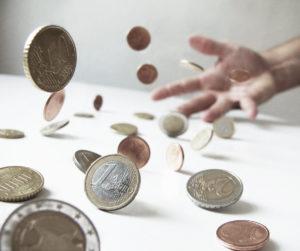 Münzen fallen auf einen Tisch
